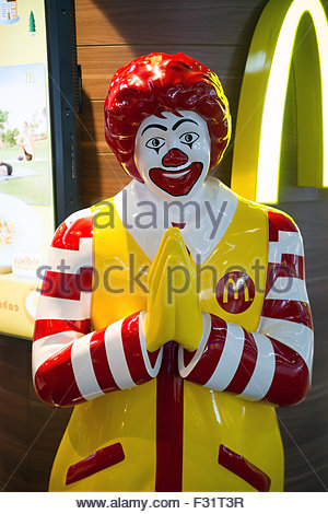 Ronald McDonald with hands joined to welcome customers in Thailand - Stock Image