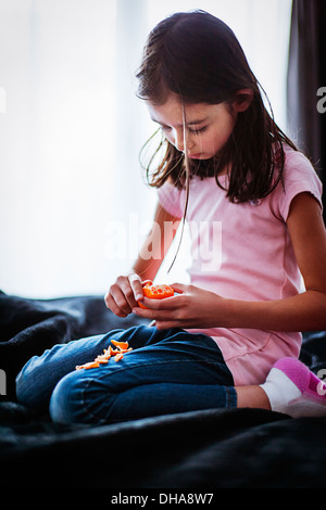 Girl peels orange - Stock Image