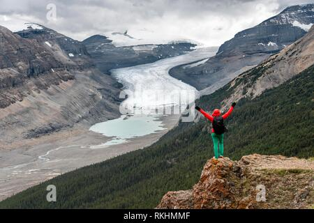 Hiker stands on a rock, stretches arms into the air, views into valley with glacier tongue, Parker Ridge, Saskatchewan Glacier, - Stock Image