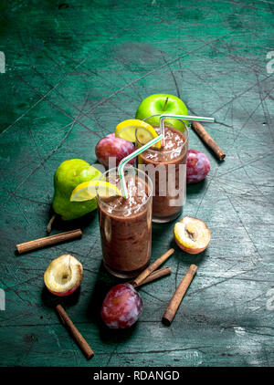 Smoothies and fresh plums, pears and cinnamon. On rustic background. - Stock Image