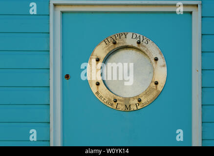 Beach hut detail with old porthole - Stock Image