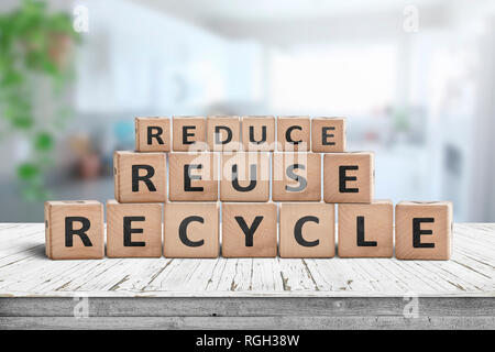 Reduce, reuse and recycle sing on a wooden desk woth a fresh bright background - Stock Image