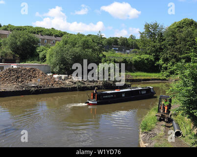 """Canal narrow boat """"Harlequin"""" makes a tight turn as it passes Finsley Gate wharf  on the Leeds and Liverpool canal in Burnley on a sunny day. - Stock Image"""