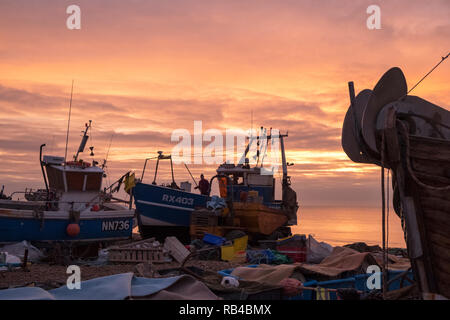 Hastings East Sussex UK. Very mild start to the day at sunrise on the Stade Fishermens beach as fishermen start loading their boats. Hastings has the largest beach-launched fishing fleets in Europe. - Stock Image