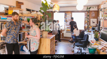 Creative business people talking, working in office - Stock Image