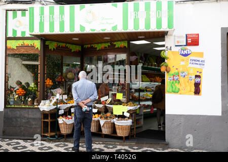 A man stands outside a fruit and vegetable shop in The Azores - Stock Image
