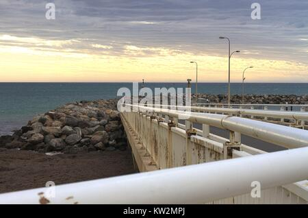 Concrete pier leading out to a rocky breakwater, view of the ocean and sunset. - Stock Image