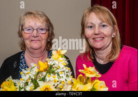 Ballydehob, West Cork, Ireland. 20th March, 2019. Despite the rain, volunteers were out collecting for the annual Irish Cancer Society's Daffodil Day in various locations around West Cork this morning. The annual fund raising coffee morning took place in Ballydehob Community Hall. Pictured at the event are Maureen Hegarty, Ballydehob and Mary O'Driscoll from Baltimore. Credit: Andy Gibson/Alamy Live News. - Stock Image