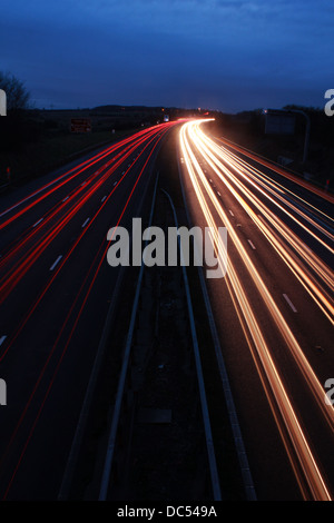 Motorway at night with car light trails - Stock Image