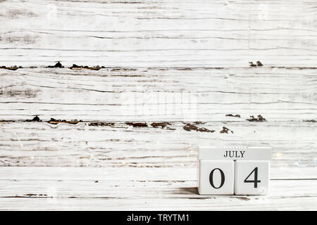 Fourth of July Background. Wood calendar blocks with the date July 4th to mark America's Independence Day against a white rustic wooden background. - Stock Image