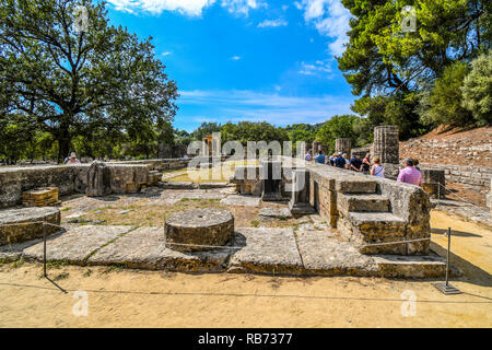 A summer day as tourists visit the ancient Greek ruins in the Greek city of Olympia. - Stock Image