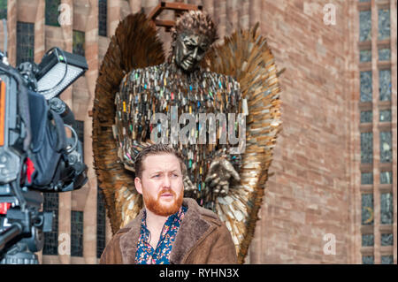Coventry, West Midlands, UK. 14th March, 2019.  The Knife Angel, which is made up of 100,000 knives which were handed into police forces around the country, was erected outside Coventry Cathedral today. The Knife Angel is a 27 foot high sculpture composed of knives by the artist Alfie Bradley as a physical reminder of the effects of violence and aggression. It is in Coventry until 23rd April. Alfie Bradley, the sculptor responsible for the Knife Angel, was interviewed.  Credit: Andy Gibson/Alamy Live News. - Stock Image