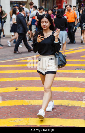 A young woman crossing the road near Times Square in Hong Kong - Stock Image