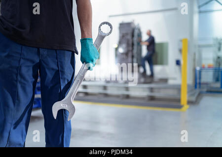 Apprentice engineer holding large spanner in gearbox factory - Stock Image