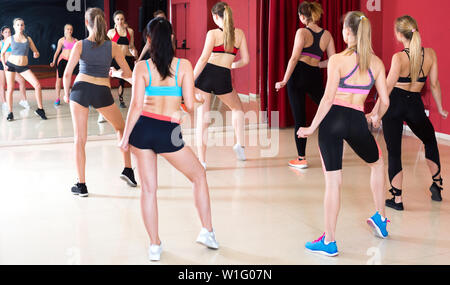 Women are practising rouch movement in jazz dance in fitness-gym. - Stock Image