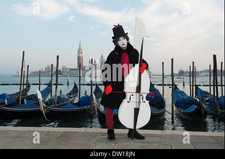Venice, Italy. 25th Feb, 2014. A male mime plays a large cello with a pegbox and scroll shaped like the front of a gondola which are also present in the background. Venice Carnivale - Tuesday 25th February. Credit:  MeonStock/Alamy Live News - Stock Image