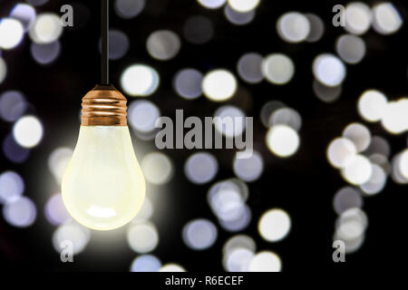 Illuminating light bulb hanging with colorful blurred Christmas lights bokeh effect and copy space. - Stock Image