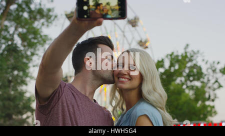 Low angle view of smiling couple kissing and taking selfie with smartphone camera outdoors - Stock Image