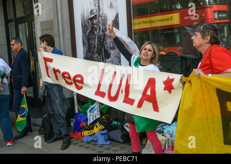 London, UK. 13th August 2018.  Brazilians hold a 'Free Lula' banner at the protest outside the Brazilian embassy calling for the release of Luiz Inacio Lula da Silva, a former trade union leader who was President of Brazil from 2003-11 to enable him to stand for election again in October. Credit: Peter Marshall/Alamy Live News - Stock Image