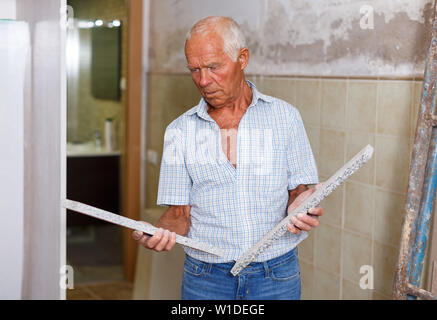 Senior man inspecting faux stone for interior renovation work in his apartment - Stock Image