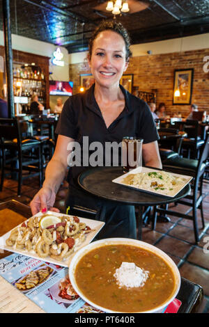 Lakeland Florida Harry's Seafood Bar & Grille restaurant interior waitress server serving calamari bowl gumbo soup employee working lunch plates - Stock Image