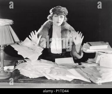 Surrendering to an abundance of paperwork - Stock Image
