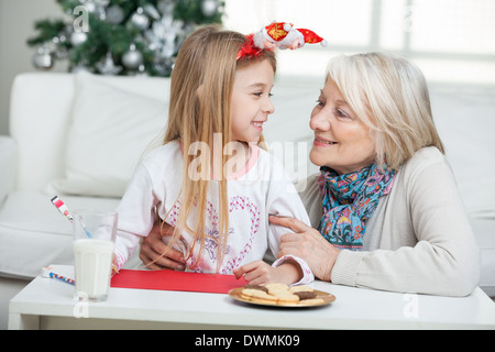 Grandmother And Girl With Cardpaper Looking At Each Other - Stock Image