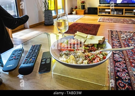 Healthy meal in front of the television. Salads, cheese and bread with a glass of white wine. - Stock Image