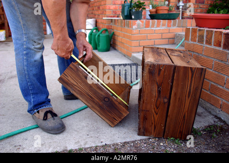 A man measures a box. - Stock Image