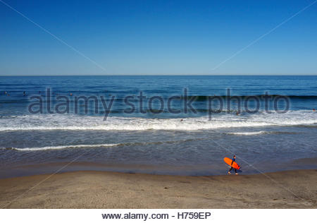 A surfer walks along the beach as other surfers await breaking waves, in Del Mar (San Diego County) in California, - Stock Image