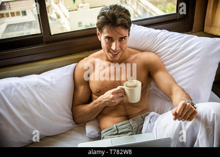 Naked young man with muscular body on bed with mug or cup in hand with coffee or tea, looking at camera - Stock Image