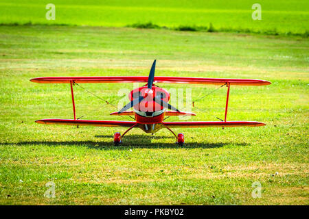 Red veteran plane ready to take off from a green meadow in the summer - Stock Image