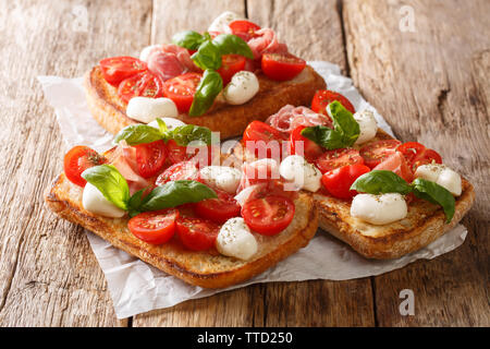 Ciabatta summer toasts with mozzarella, tomatoes, ham and basil close-up on the table. horizontal - Stock Image