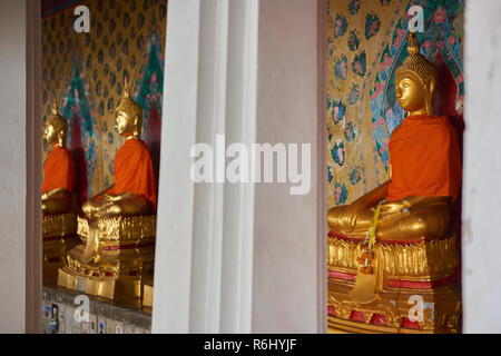 Three of the several golden Buddha statues lined up in a diminishing perspective under the cover of one of the Ordination Hall in Bangkok, Thailand. - Stock Image