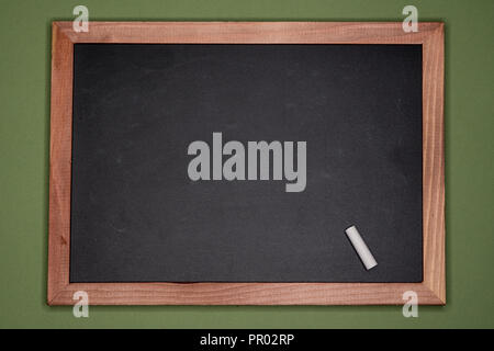 Empty chalk board with wooden frame on green background, blank copy space. A piece of chalk on blackboard - Stock Image