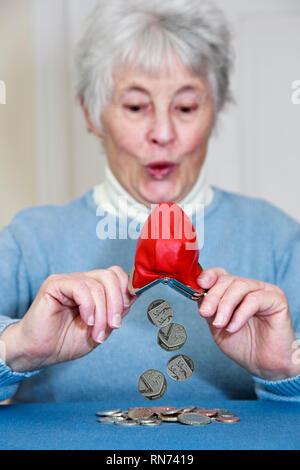 Composite image of a wealthy senior elderly woman with a surprised expression emptying a pile of money out of a purse. England UK Britain - Stock Image