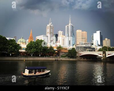 Melbourne skyline with a boat on the Yarra river during stormy weather - Stock Image