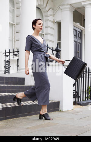 Chic young woman in jumpsuit leaving smart London terrace - Stock Image