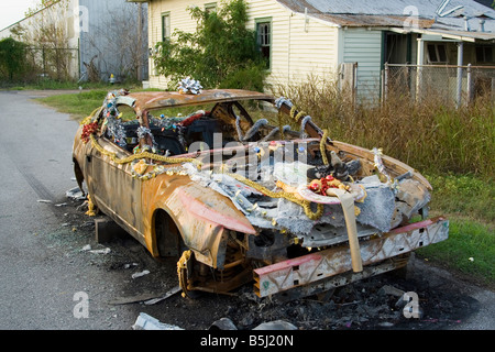 Burned Ford Mustang in the Lower Ninth Ward of New Orleans Louisiana - decorated for Christmas. - Stock Image
