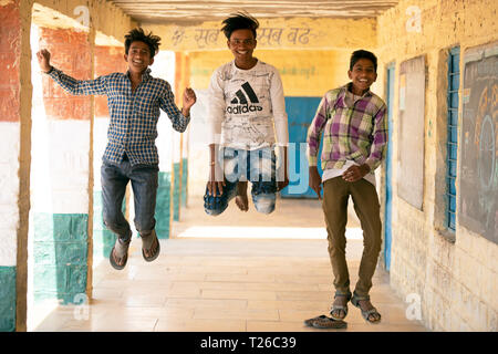 Young Bhil tribe boys acting silly, fooling around outside their village school in Rajasthan, India. - Stock Image