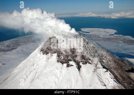 A steam plume rises from the snow-covered lava dome at the summit of Augustine Volcano on Augustine Island in the - Stock Image