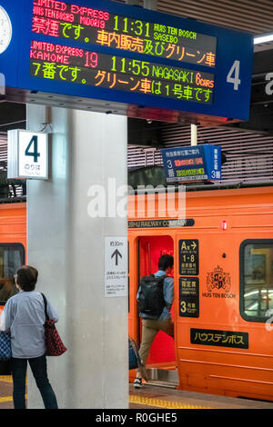 A special orange JR Kyushu Rail train to Huis Ten Bosch theme park in Sasebo is about to depart from Fukuoka Hakata Station. - Stock Image