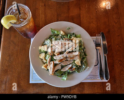 Chicken Caesar Salad and a glass of ice tea, from above, on a restaurant table. - Stock Image