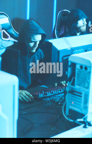 Young hooded programmers sitting at one table and using powerful computers while working on web script - Stock Image