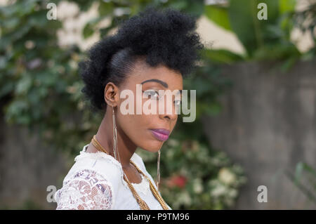 Portrait of young African woman posing in a garden. - Stock Image