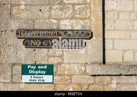 Wall showing edge of bricked up window with 3 signs fixed to it, Pay and Display, No Cycling, and To Swimming pool - Stock Image