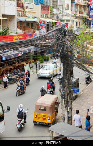 A mesh of electric cables  hangs from a lamp post in busy street in the historical part of town in Phnom Penh, Cambodia. Shot from above. - Stock Image