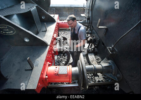 The fireman of 9F 2-10-0 Steam Locomotive number 92203 'Black Prince' uncouples the Engine from its coaches - Stock Image