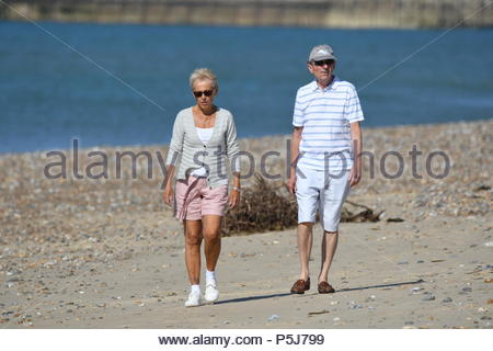 Littlehampton, UK. Wednesday 27th June 2018. A couple of people take a stroll on the beach on another very warm and sunny morning in Littlehampton, on the South Coast. Credit: Geoff Smith / Alamy Live News. - Stock Image