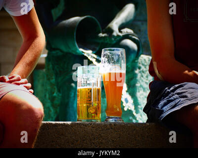 Tourists sitting at water fountain drinking beer at Marienplatz Munich Germany Europe - Stock Image